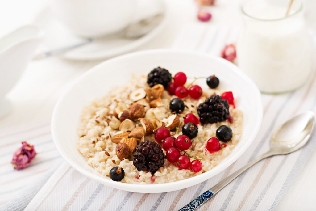 Tasty and healthy oatmeal porridge with berry, flax seeds and nuts. Healthy breakfast. Fitness food. Proper nutrition.