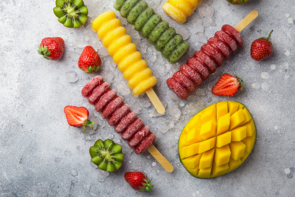 set of colorful popsicles with fresh fruits and berries, top view